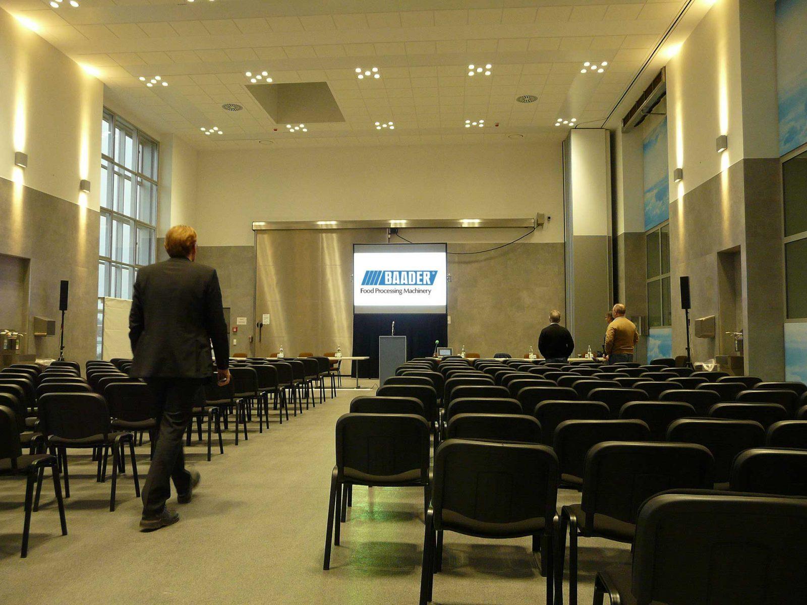 Tafeslichttaugliche Großbildprojektion in einer Halle mit großen Glasflächen.
