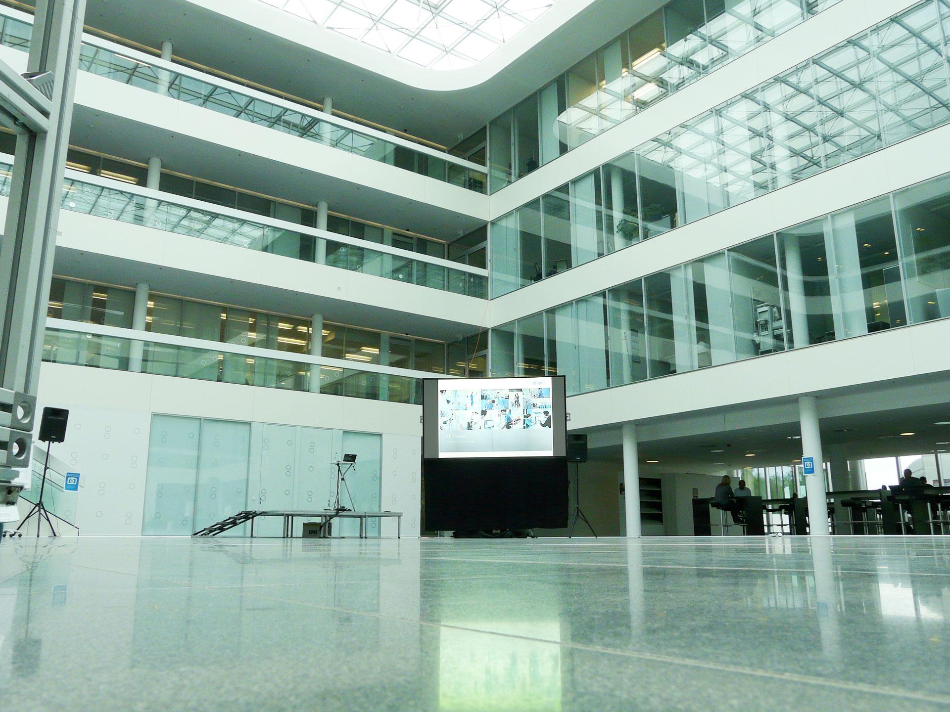Tageslichtprojektion mit einem 2K Kinoprojektor und einer Revosoft Hellraumleinwand im Dräger Atrium unter einem über 500m² großem Glasdach.
