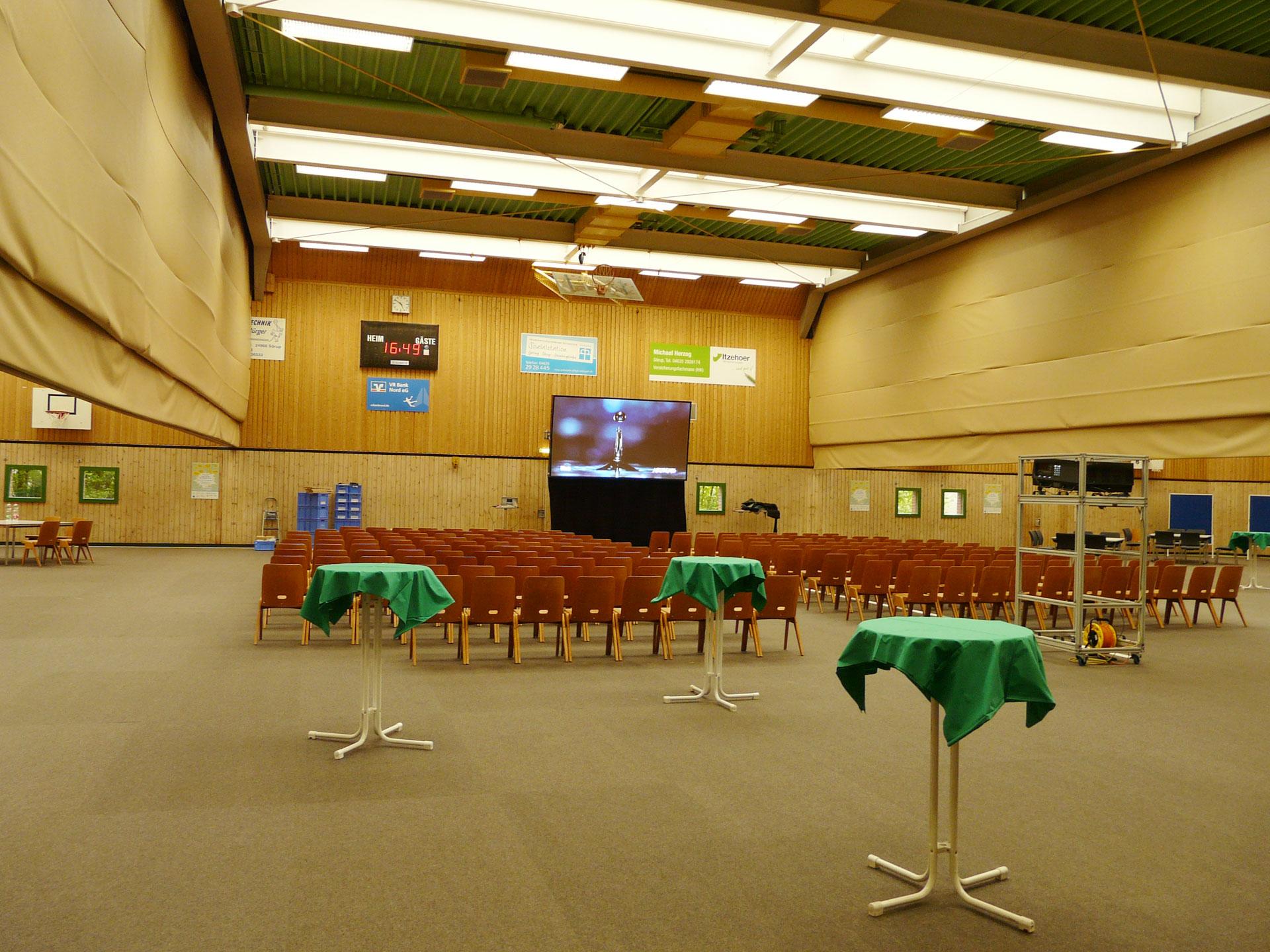 Hellraumprojektion in einer Sporthalle mit Tageslichteinfall durch große Deckenlichter.